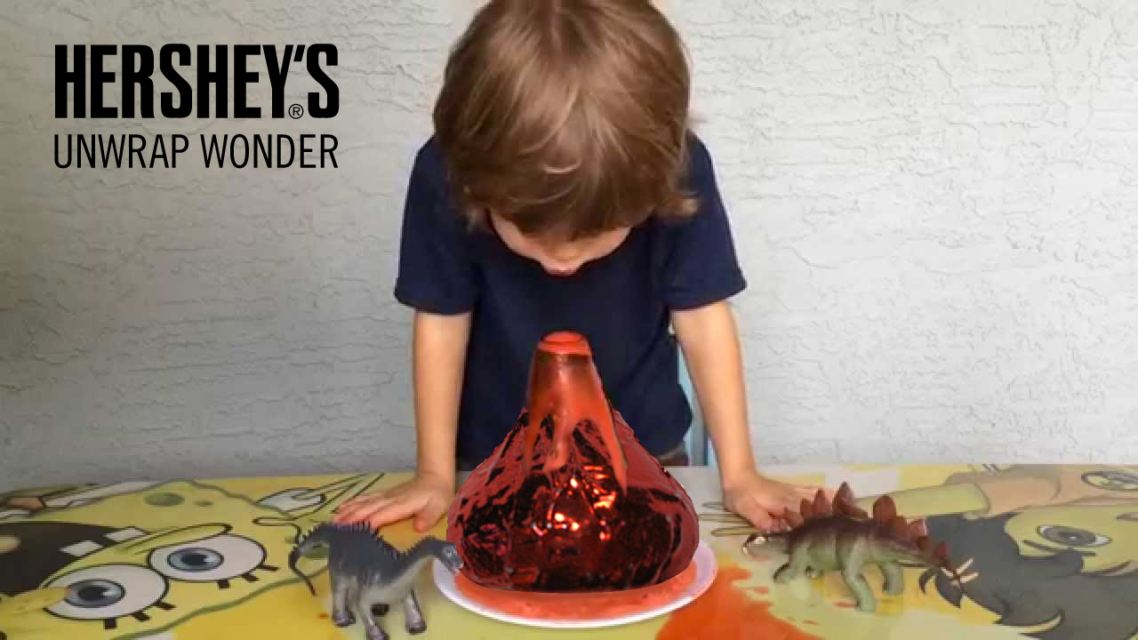 unwrap wonder: a kid looking at volcano science experiment with a red kiss in place of the volcano